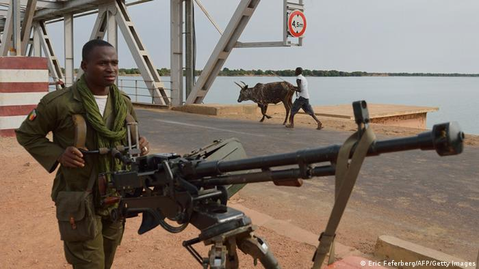 A Malian soldier holds a machine gun as he stands guard at the entrance of a strategic bridge over the Niger river on January 22, 2013, near Markala, some 270km north of Bamako. Mali's army chief today said his French-backed forces could reclaim the northern towns of Gao and fabled Timbuktu from Islamists in a month, as the United States began airlifting French troops to Mali. AFP PHOTO / ERIC FEFERBERG (Photo credit should read ERIC FEFERBERG/AFP/Getty Images)