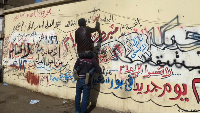An Al-Ahly fan scrawls graffiti on a wall (Matthias Sailer)
