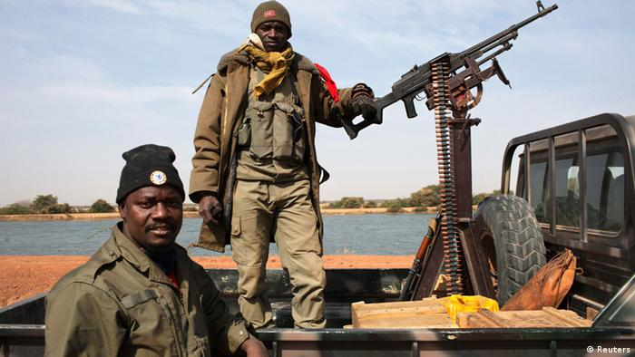 Malian soldiers stand guard in a Malian army pickup truck mounted with a machine gun in Diabaly January 26, 2013. REUTERS/Joe Penney (MALI - Tags: MILITARY CIVIL UNREST POLITICS CONFLICT)