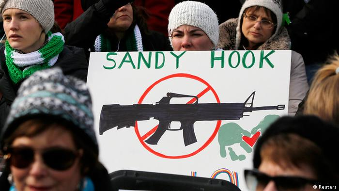Demonstrator in Washington holds up sign that reads 'Sandy Hook,' and below it is a picture of an assault rifle insidea red circle with a line through it.