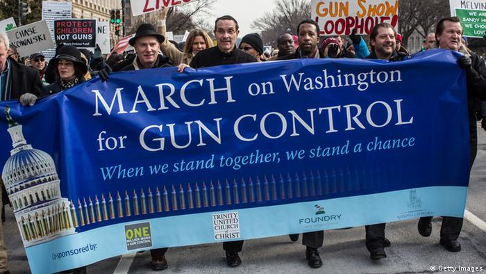 Gun control advocates march in Washington, carrying banners.