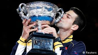 Novak Djokovic of Serbia kisses the Norman Brookes Challenge Cup after defeating Andy Murray of Britain in their men's singles final match at the Australian Open tennis tournament in Melbourne, January 27, 2013. Djokovic became the first man to win three successive Australian Open titles in the professional era. REUTERS/Daniel Munoz (AUSTRALIA - Tags: SPORT TENNIS TPX IMAGES OF THE DAY)