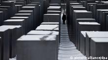 Ein Mann geht am 25.01.2013 in Berlin zwischen den Stelen des Denkmals für die ermordeten Juden Europas, des sogenannten Holocaust-Mahnmals. Am 27.01.2013 ist der Gedenktag für die Opfer des Nationalsozialismus. Foto: Michael Kappeler/dpa