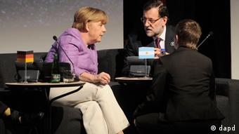 Germany's Chancellor Angela Merkel (L) talks to Spain's Prime Minister Mariano Rajoy