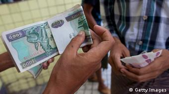 Myanmar currency being exchanged (Photo by Paula Bronstein/Getty Images)
