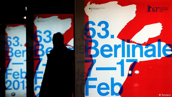 A pedestrian walks past an illuminated advertising banners for the upcoming 63rd Berlinale film festival in Berlin January 24, 2013. The Berlinale film festival runs from February 7 to 17 in the German capital. REUTERS/Fabrizio Bensch (GERMANY - Tags: ENTERTAINMENT)