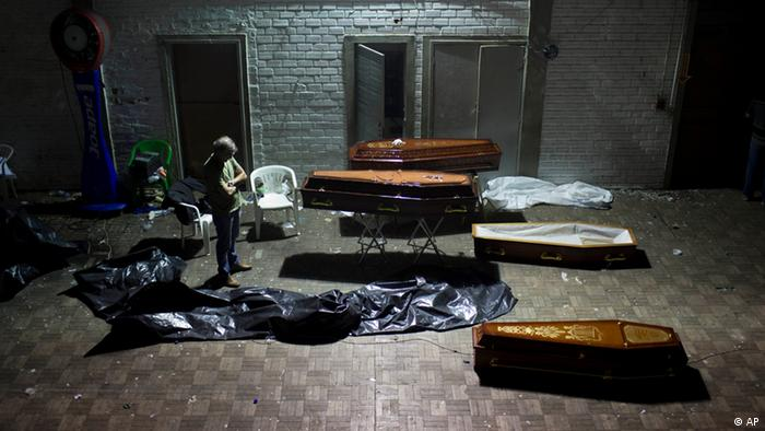 A man stands around coffins containing the remains of victims after the bodies were identified at a gymnasium in Santa Maria (Photo: Felipe Dana/AP/dapd)
