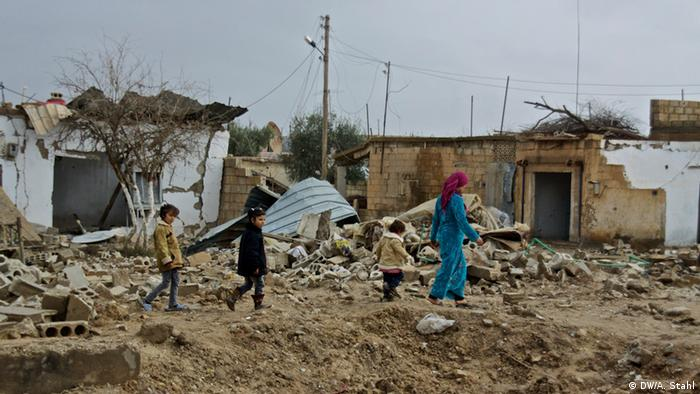 A woman escorts her children through the rubble of their destroyed village. Ras al-Ain, Syria (Photo: Andreas Stahl)