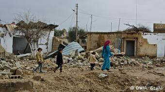A woman escorts her children safely through the rubble of their destroyed village. Ras al-Ain, Syria *** Deutsche Welle, Andreas Stahl, 21.12.2012, 13:39:21
