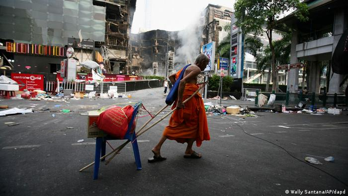 In this May 20, 2010, picture, an elderly monk drags a chair with his belongings past the burnt out Central World shopping mall in Bangkok, a day after it was set on fire by anti-government protesters. (Photo:Wally Santana/AP/dapd)