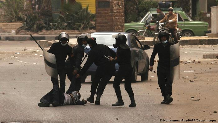 Egyptian riot policemen drag a protester along the ground during clashes near Cairo's Tahrir Square on January 28, 2013. Egypt's cabinet approved a draft law that would allow President Mohamed Morsi to deploy the armed forces on the streets 'to participate with the police in preserving security and protecting vital establishments.' AFP PHOTO/MOHAMMED ABED (Photo credit should read MOHAMMED ABED/AFP/Getty Images)