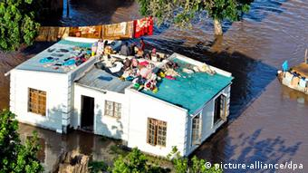 epa03557393 People take shelter on the roof of a house during the floods at Xai-Xai, Gaza Province, Mozambique, 26 January 2013. At least five people died in floods in southern Mozambique, the National Institute of Disaster Management (INGC) said on 25 January, as efforts to evacuate tens of thousands of people in affected areas continued. Officials are calling for up to 55,000 people in affected areas to evacuate their homes. In 2000, heavy rains killed 700 people and affected 1 million more. EPA/ANTONIO SILVA +++(c) dpa - Bildfunk+++