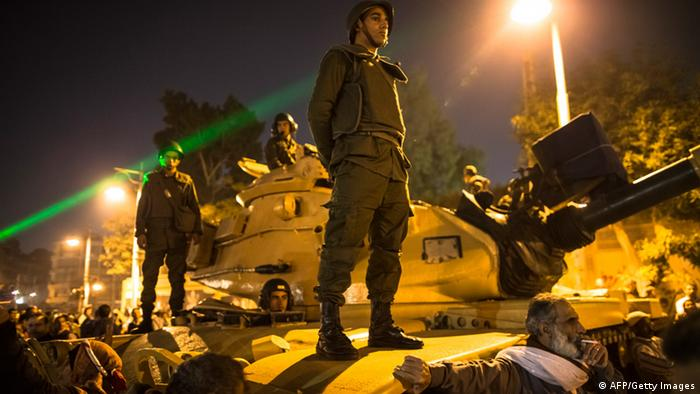 CAIRO, EGYPT - DECEMBER 18: Egyptian soldiers stand guard as protestors opposing President Mohammed Morsi chant slogans during a demonstration at the Presidential Palace on December 18, 2012 in Cairo, Egypt. Hundreds of people gathered in front of the Presidential Palace and in Tahrir Square to protest against President Mohammed Morsi and the alleged rigging of the first round of voting in the constitutional referendum. (Photo by Daniel Berehulak/Getty Images)