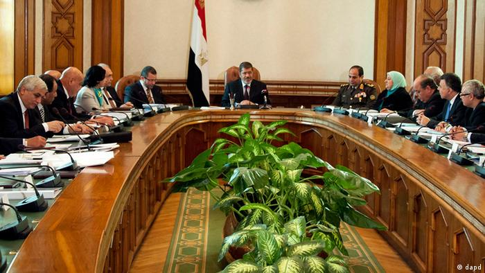rFILE - In this Sunday Jan. 6, 2013 file image released by the Egyptian Presidency, President Mohammed Morsi, center, meets with his cabinet including 10 new ministers after their swearing in at the presidential palace in Cairo, Egypt. As Egypt begins the latest round of talks with the International Monetary Fund for a $4.8 billion loan, the government says it will boost international confidence in its economy. However, critics question whether the president's Muslim Brotherhood group has the ability to carry out unpopular austerity measures ahead of crucial parliamentary elections that will take place in the coming months. (Foto:Egyptian Presidency, File/AP/dapd)
