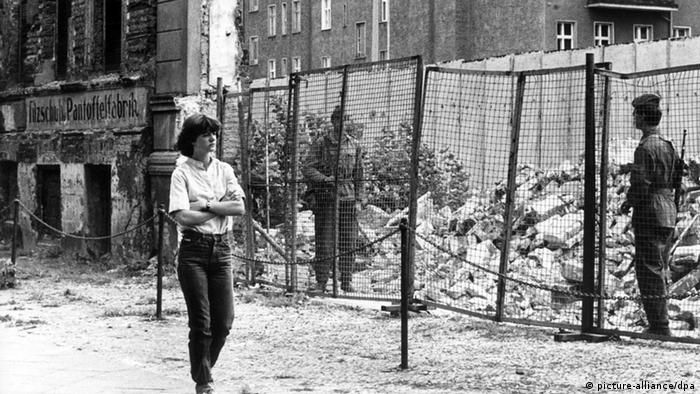 A woman walks past a crumbling facade and a pile of rubble in 1980 (picture-alliance/dpa)