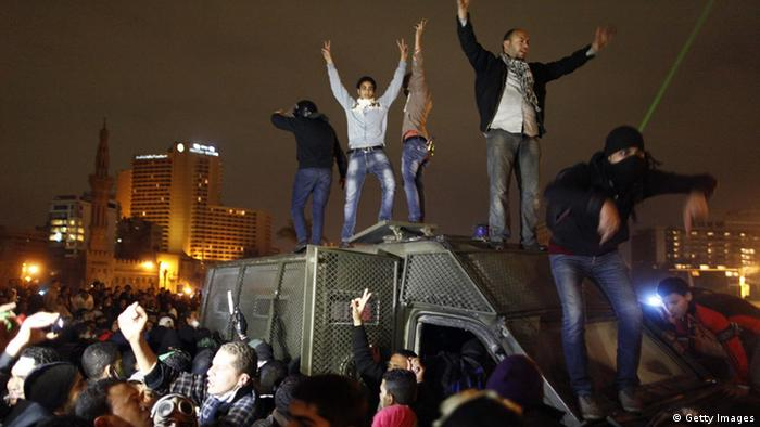 Egyptian protesters stand on a police vehicle before they set it on fire in Cairo's Tahrir Square on January 28, 2013. Egypt's main opposition bloc rejected an invitation by President Mohamed Morsi for talks on the violence and political turmoil sweeping the country and instead called for fresh mass demonstrations. AFP PHOTO / MAHMOUD KHALED (Photo credit should read MAHMOUD kHALED/AFP/Getty Images)