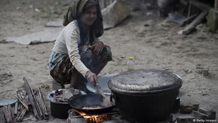 This picture taken on November 14, 2012 shows a woman cooking food outside her schack at a slum in Bago.