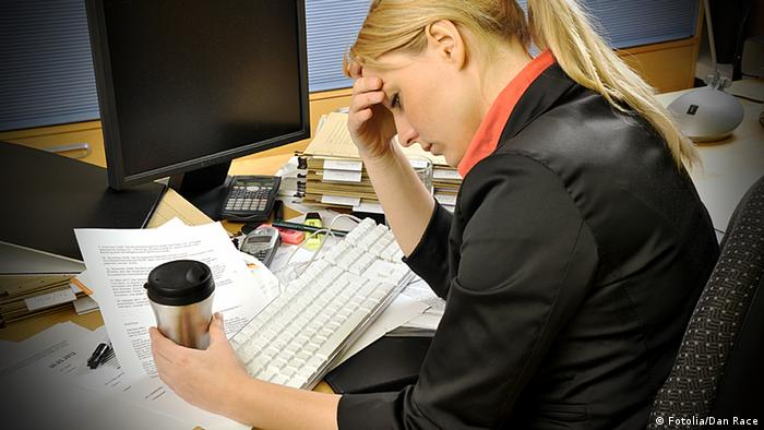 A woman sits at a desk, hunched over a keyboard and scattered papers. She nurses a coffee in one hand and holds her forehead in the other.