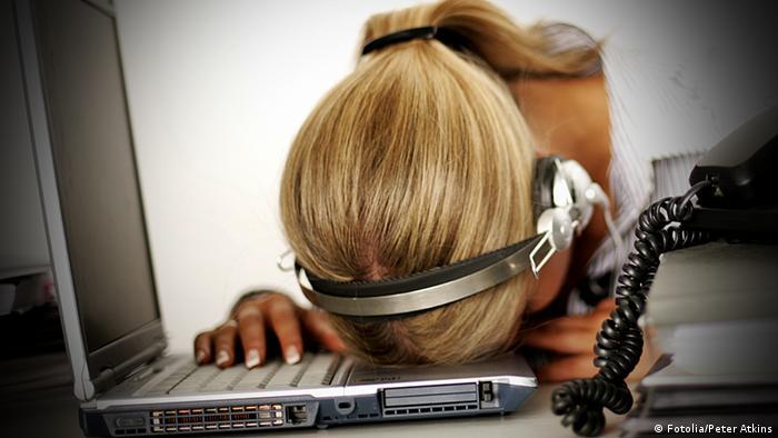 Eine Frau liegt mit ihrem Kopf und Headset auf der Tastatur eines Laptops