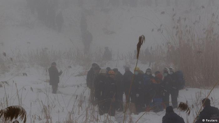 Emergency and security personnel are seen through a heavy fog about 100 metres (328 feet) from the site of the plane crash near Almaty January 29, 2013. (Photo: REUTERS/Shamil Zhumatov)