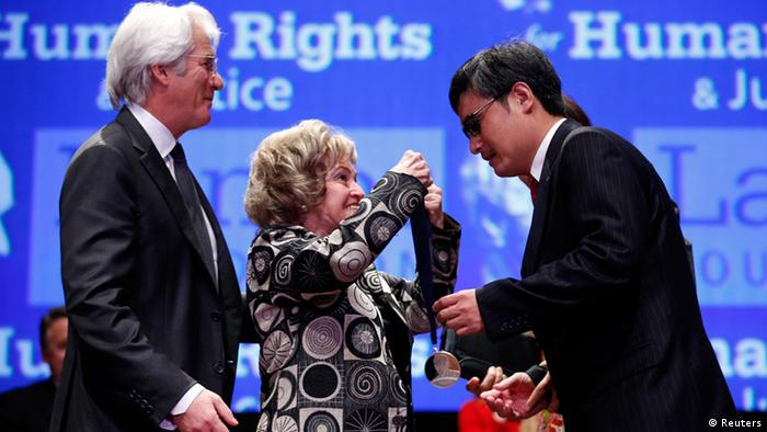 Chinese dissident Chen Guangcheng receives The Tom Lantos Human Rights Prize in the Capitol in Washington January 29, 2013. Presenting the award is the widow of Tom Lantos, Annette Lantos. Actor Richard Gere stands behind her. REUTERS/Kevin Lamarque (UNITED STATES - Tags: POLITICS ENTERTAINMENT)