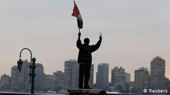A protester opposing Egyptian President Mohamed Mursi stands on Kasr Elnile bridge holding the Egyptian flag during clashes with riot police along Qasr Al Nil bridge, which leads to Tahrir Square, in Cairo January 28, 2013. A man was shot dead on Monday in a fifth day of violence that has killed 50 Egyptians and prompted the Islamist president to declare a state of emergency in an attempt to end a wave of unrest sweeping the biggest Arab nation. REUTERS/Mohamed Abd El Ghany (EGYPT - Tags: POLITICS CIVIL UNREST)