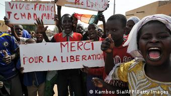People hold a sign reading 'Thank you for the liberation' in Ansongo, a town south of the northern Malian city of Gao. AFP PHOTO / KAMBOU SIA (Photo credit should read KAMBOU SIA/AFP/Getty Images)