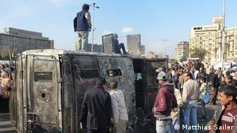 Protesters stand on top of a burnt-out police transport van during the day Copyright: Matthias Sailer
