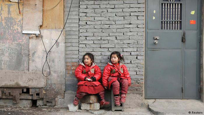 Two 4-year-old twin sisters rest against a wall at a poor residential area for migrant workers on the outskirts of Beijing January 12, 2013. Chinese rural children are expected to get better care from the government including more nutritious meals, safe school buses and better accommodation facilities. Currently, China has about 58 million rural children living away from their parents, or 28.29 percent of the total number of rural children, Xinhua reported. REUTERS/Jason Lee (CHINA - Tags: POLITICS SOCIETY IMMIGRATION POVERTY)
