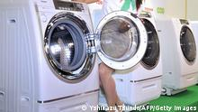 A model displays the new washing and drying machine of Japanese electronics giant Toshiba 'TW-5000' which achieves low power consumption and conserving water at the company's headquarters in Tokyo on August 5, 2008. The new washing machine also has function of air conditioner which enables to cool at laundry room during summertime and warm during winter season. AFP PHOTO / Yoshikazu TSUNO (Photo credit should read YOSHIKAZU TSUNO/AFP/Getty Images)
