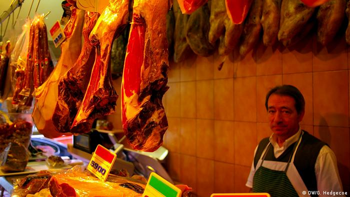 Hidden behind a hanging row of cured Spanish ham, a Spanish man smiles at the camera (Photo: Guy Hedgcoe for DW)