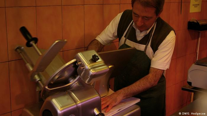 A man slices meet with an industrial meat slicer (Photo: Guy Hedgecoe for DW)