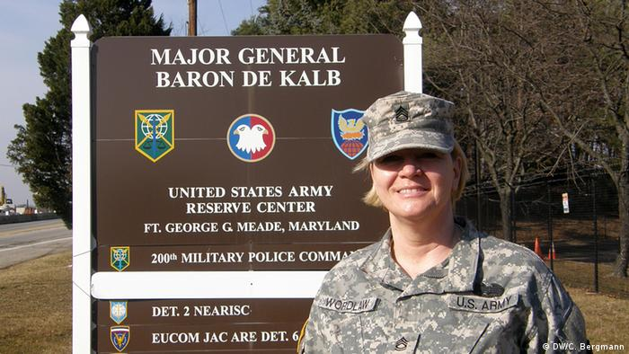 A smiling blond-haired woman in light battle dress uniform stands in front of a brown sign which says that she is in Fort Meade, Maryland (Photo: DW/Christina Bergmann)