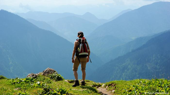 A hiker enjoys a spectacular view of mountain scenery
