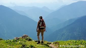 Ein Wanderer steht auf einem Berg und blickt bei klarer Sicht und Sonne auf die umliegenden Berge