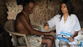 Balakrishna Bhudaji (L) is examined by a doctor from the Bombay Leprosy Project (BLP) during a field visit to Chincvali village, some 100 kms from Mumbai on May 15, 2009. (Photo: PAL PILLAI/AFP/Getty Images)
