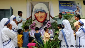 Indian nuns and orphans offer prayers in front of a portrait of the late Mother Teresa during the commemoration of her 12th death anniversary at Nirmala Sishu Bhavan in Ahmedabad on September 5, 2009. (Photo: SAM PANTHAKY/AFP/GettyImages)