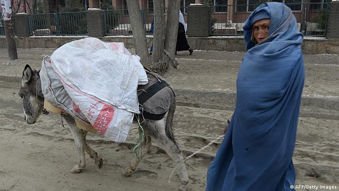 A burqa-clad Afghan woman walks with her donkey on a cold day in Kabul on January 8, 2013. Despite Afghanistan receiving billions of dollars of aid since 2001, more than 100 children died last year during the harshest winter in two decades, and the UN refugee agency UNHCR has co-ordinated efforts to reduce repeat fatalities. AFP PHOTO/ SHAH Marai (Photo credit should read SHAH MARAI/AFP/Getty Images)