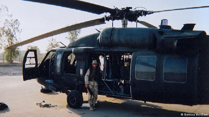 A woman in desert battle dress uniform stands in front of a black helicopter. (Photo: copyright Bettina Wordlaw)