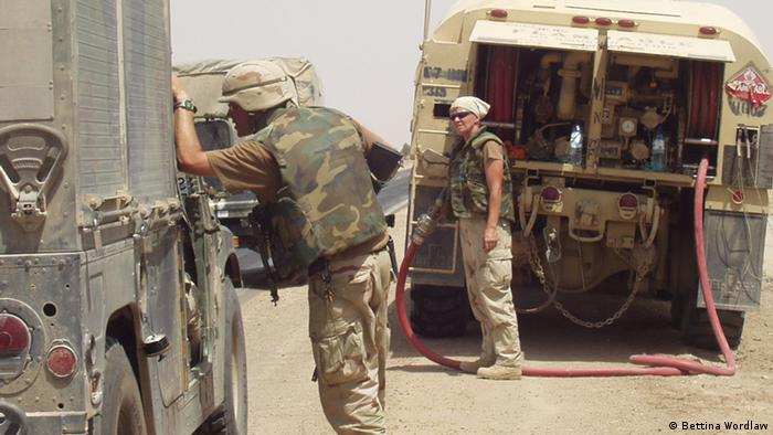 In a deser setting, a female soldier refuels a truck while a male soldier inspects another. (Photo: copyright Bettina Wordlaw)
