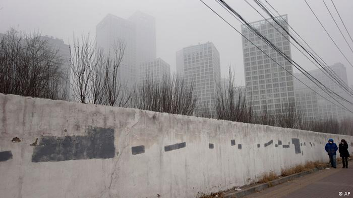 A man and woman wearing masks walk along a wall near a smog-shrouded residential district in Beijing Tuesday, Jan. 29, 2013. Extremely high pollution levels shrouded eastern China for the second time in about two weeks Tuesday, forcing airlines in Beijing and elsewhere to cancel flights because of poor visibility and prompting government warnings for residents to stay indoors. (Foto:Ng Han Guan/AP/dapd)