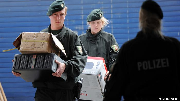 Policemen carry boxes and computers on June 14, 2012 during a raid at the Millatu Ibrahim Mosque in Solingen, western Germany. German police carried out raids in seven different regional states targeting individuals suspected of belonging to radical Islamic Salafist groups, the interior ministry said. At the same time, Interior Minister Hans-Peter Friedrich banned one particular network known as Millatu Ibrahim. AFP PHOTO / HENNING KAISER GERMANY OUT (Photo credit should read HENNING KAISER/AFP/GettyImages)