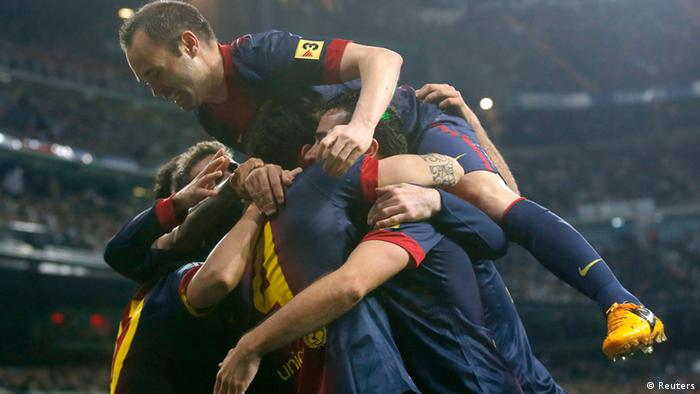 Barcelona's Andres Iniesta (top) and teammates celebrates Cesc Fabregas' goal against Real Madrid during their Spanish King's Cup semi final first leg soccer match at Santiago Bernalbeu stadium in Madrid January 30, 2013. REUTERS/Juan Medina (SPAIN - Tags: SPORT SOCCER)