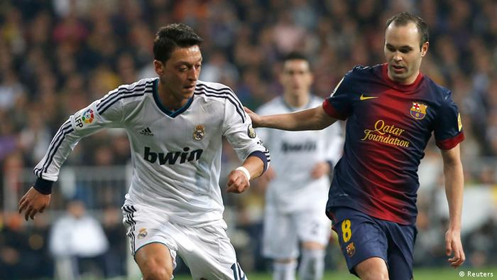 Real Madrid's Mesut Ozil (L) fights for the ball with Barcelona's Andres Iniesta during their Spanish King's Cup semi final first leg soccer match at Santiago Bernabeu stadium in Madrid, January 30, 2013. REUTERS/Juan Medina (SPAIN - Tags: SPORT SOCCER)