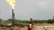 ARCHIV - Nigerianische Arbeiter der Akon Oil Company gehen an einer lodernden Flamme an einer Öl-Leitung im Niger-Delta in der Nähe von Port Harcourt vorbei (Archivfoto vom 01.02.2006). Das Niger-Delta besitzt zwar reiche Erdölvorkommen, der Großteil der Bevölkerung lebt jedoch in bitterer Armut und leidet unter der Umweltverschmutzung, welche die Öl-Industrie mit sich bringt. Seit einem Jahr hat sich die Sicherheitslage für ausländische Arbeiter dramatisch zugespitzt, seit Anfang des Jahres wurden bereits knapp 60 Menschen entführt. Foto: EPA (zu dpa-Reportage: Drama im Delta - Entführungswelle bedroht nigerianische Ölindustrie vom 19.03.2007) +++(c) dpa - Bildfunk+++