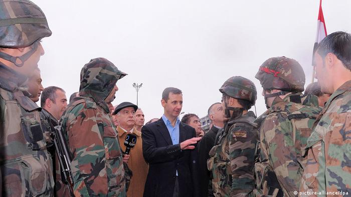 epa03161396 A handout photo made available by the official Syrian Arab News Agency (SANA) shows Syrian President Bashar Assad (L) speaking with soldiers as he tours the Baba Amr neighborhood in the central province of Homs, Syria, 27 March 2012. Reports quoting Syrian state-run media said that Assad on 27 March toured the restive area of Baba Amr in Homs, the site of heavy clashes between rebels and Syrian troops earlier this month. This was the president's first visit to Baba Amr after dozens died in a month-long shelling on the area in February. EPA/SANA/HANDOUT HANDOUT EDITORIAL USE ONLY/NO SALES +++(c) dpa - Bildfunk+++