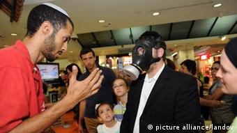A worker at a gas mask distribution center helps an Israeli man try on a gas mask in a mall in Jerusalem, Israel, August 23, 2012. Photo: UPI/Debbie Hill /LANDOV pixel