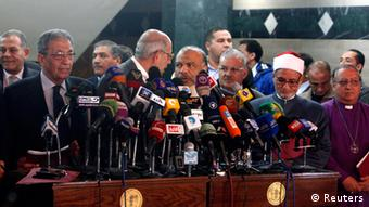 Standing behind a jumbled array of microphones attached to multiple podiums, Egyptian politicians jockey for a position to speak (Photo: REUTERS/Asmaa Waguih)