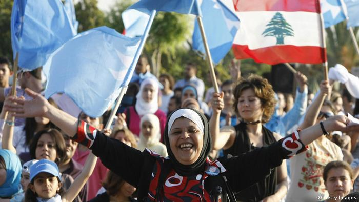Supporters of Lebanese Prime Minister Fuad Siniora and Education Minister Bahiya Hariri wave national flags (R) and the blue banner of the Mustaqbal movement during a celebration rally at the latter's villain Majdelyoun, in the hills east of the southern port city of Sidon on June 8, 2009, following the victory of her Western-backed coalition in the general elections. In Beirut, celebratory gunfire rattled through the capital, fireworks exploded and the champagne flowed after a March 14 coalition declared victory over the Hezbollah-led opposition in Lebanon's crucial parliamentary election. Hariri is the sister of the billionaire former prime minister Rafiq Hariri who was killed in a Beirut car bombing in 2005. AFP PHOTO/RAMZI HAIDAR (Photo credit should read RAMZI HAIDAR/AFP/Getty Images)