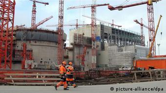 Arbeiter gehen an der Baustelle des größten Atomkraftwerk der Welt in Olkiluoto/Finnland (Bild: dpa)